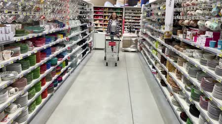 Young woman has fun riding a trolley in a supermarket. 4K Slow Mo