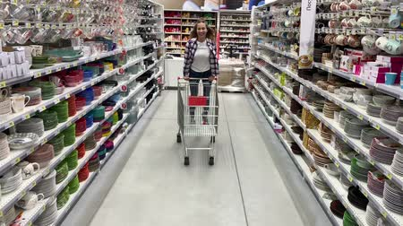 Positive young woman have fun in the supermarket. The girl rides a cart. 4K Slow Mo Stock mozgókép