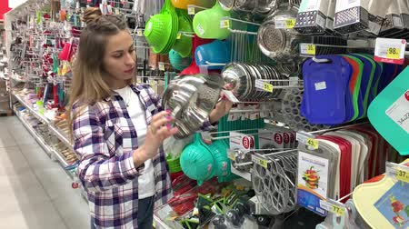 Pretty young woman chooses dishes in the hypermarket. The girl takes a friend and goes out of frame. 4K Slow Mo