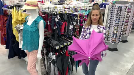 Woman chooses an umbrella in the hypermarket. The girl takes a pink umbrella, opens it and spins under it. 4K Slow Mo Stock mozgókép