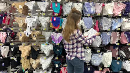 Hypermarket. Lingerie department. Young woman chooses panties. 4K Slow Mo 影像素材
