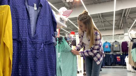 Huge store. The girl walks between the rows with clothes, takes a T-shirt and leaves. 4K Slow Mo Stock mozgókép