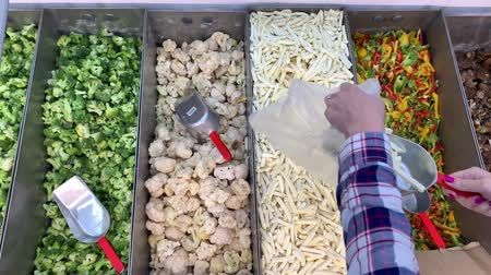 Supermarket. A woman is picking up a frozen potato into a bag. In the refrigerator are frozen vegetables. 4K Slow Mo