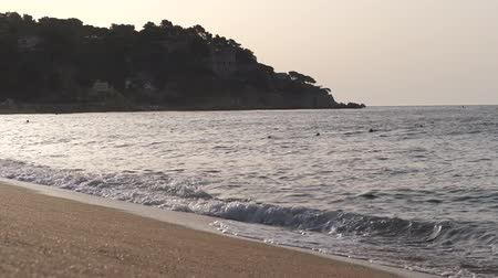 Beautiful sandy beach. At sunset the silhouette of the mountain on which the houses and the castle stand. 4K Slow Mo