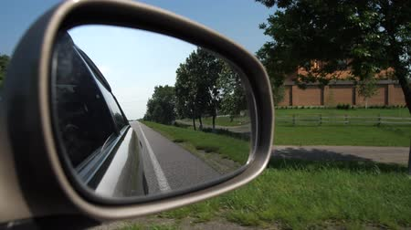 back side : Shooting through the side mirror of the car. The car moves through the countryside. 4K Slow Mo