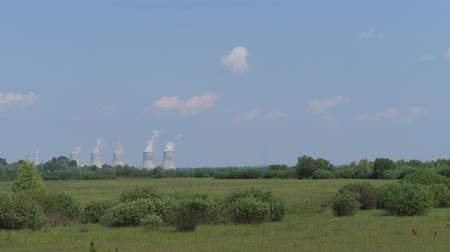 High towers in the field, with smoke coming out of them, environmental pollution. 4K Slow Mo