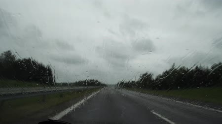 Raindrops on the car window, transport moves on the highway outside the city. 4K Slow Mo Stock mozgókép