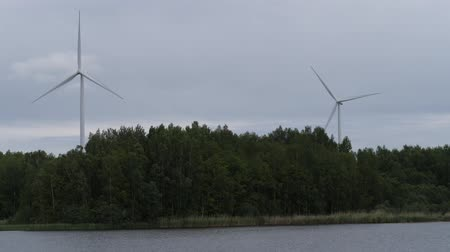 meteorological : Huge windmills stand in the forest by the lake. New technologies. 4K Slow Mo