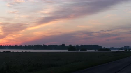 Panorama on a beautiful lake in the fog. The sunset sky is blushing above it. 4K Slow Mo Stock mozgókép