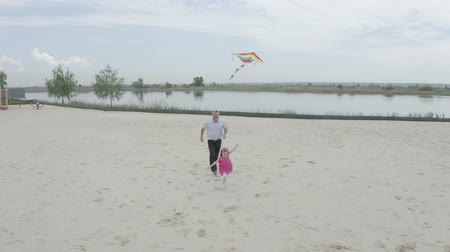 Grandfather and granddaughter launch a kite on the beach at the lake. Filming from the air. 4K Slow Mo