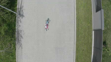 szektor : Shot from the air, the little girl rides a bicycle in the park or cottage. 4K Slow Mo Stock mozgókép
