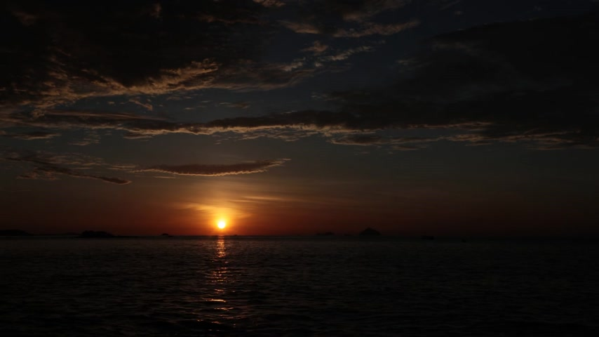 экономить : Time lapse movie with fiery orange sunrise sky looking out over the south China sea in Nha Trang Bay Vietnam. With fishing boat silhouettes.