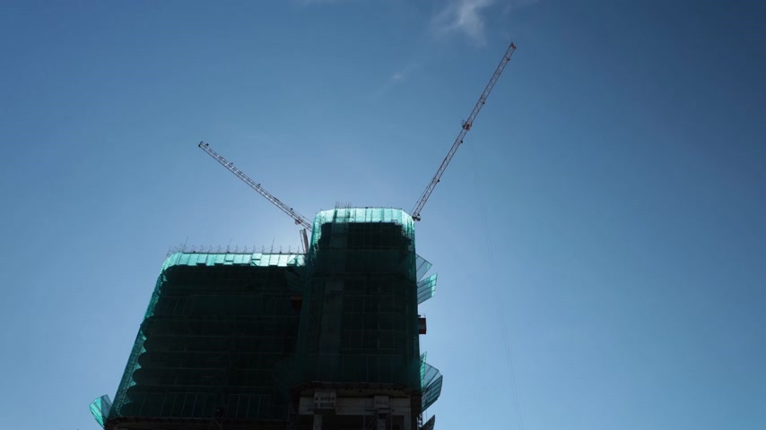 lanoví : Cranes in operation over a vietnamese construction site with clear blue skies in high definition time lapse.