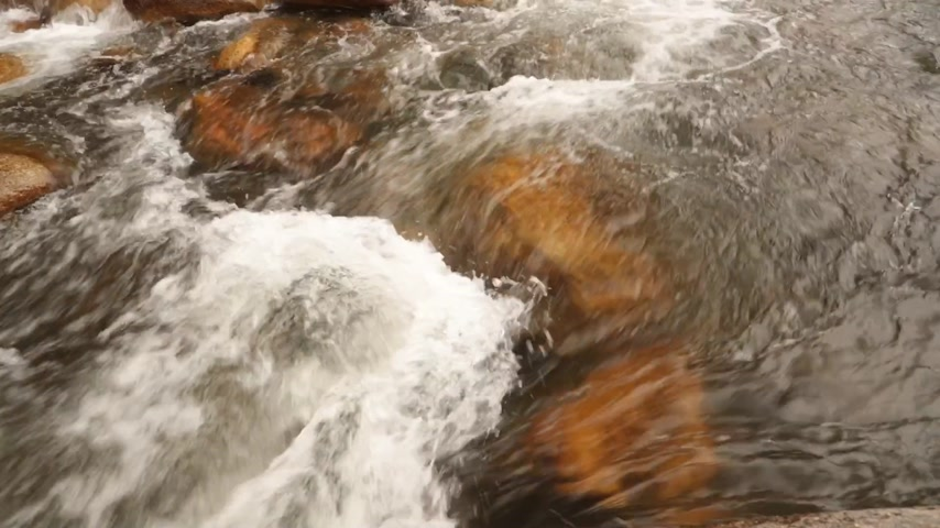 pocsolya : Rugged mountain river scenery panning panoramic with clear rushing mountain water running around large boulders, high definition stock footage movie clip. Stock mozgókép