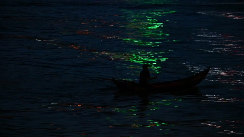small vessels : Fisherman in a small wooden fishing boat with colorful neon light reflecting off the water, low light night fishing high definition stock footage clip. Stock Footage