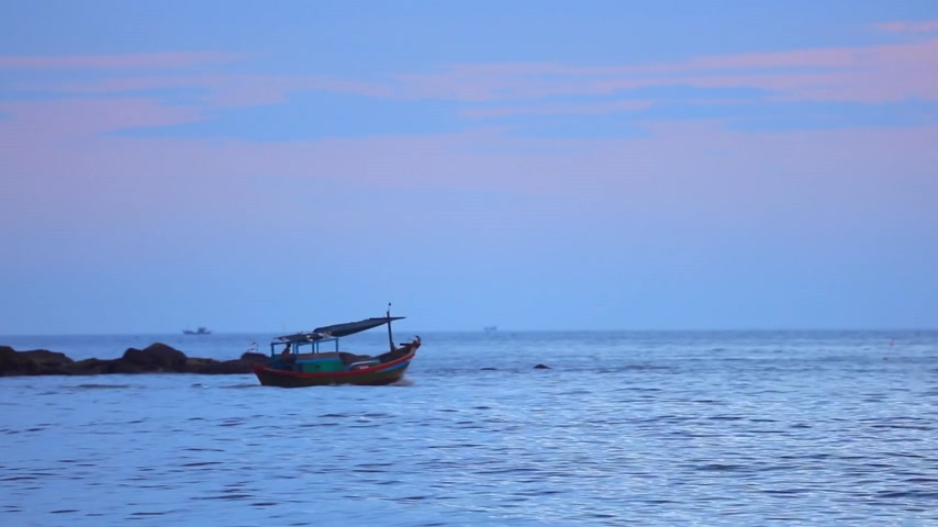 camera panning : Fisherman in a small wooden fishing boat navigating across the south china sea, under tropical sunset skies high definition stock footage clip. Stock Footage