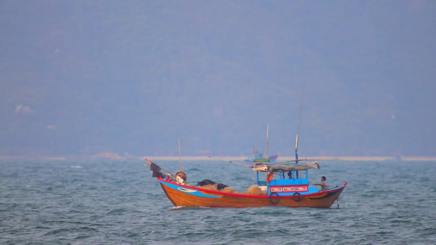 camera panning : South China Sea, Central Vietnam, Asia, August 27 2018. Vietnamese fishing boats navigating across the South China Sea, deep sea fishing in wooden boats.