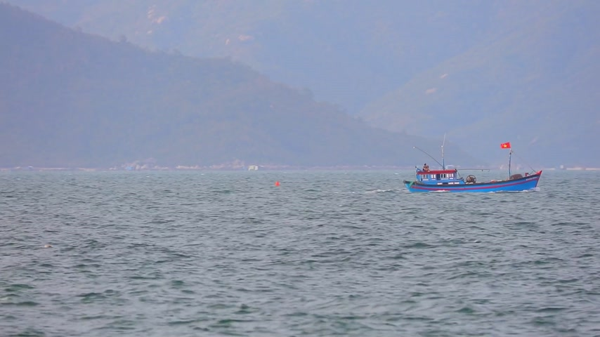 camera panning : South China Sea and small wooden fishing boats in central Vietnam with a mountainous backdrop.