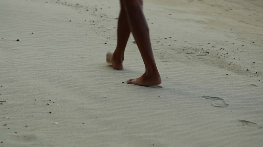 mansão : Mans feet and legs close up walking barefoot on a fresh golden sandy beach. Leaving footprints in the sand, with small rocks and sea shells scattered though out the beach. Dry white sandy beach.