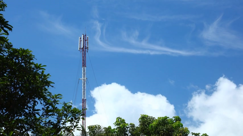 telecoms : Mobile communication mast in red and white time lapse with treetops and deep blue tropical cloudy skies. Network broadcasting tower.