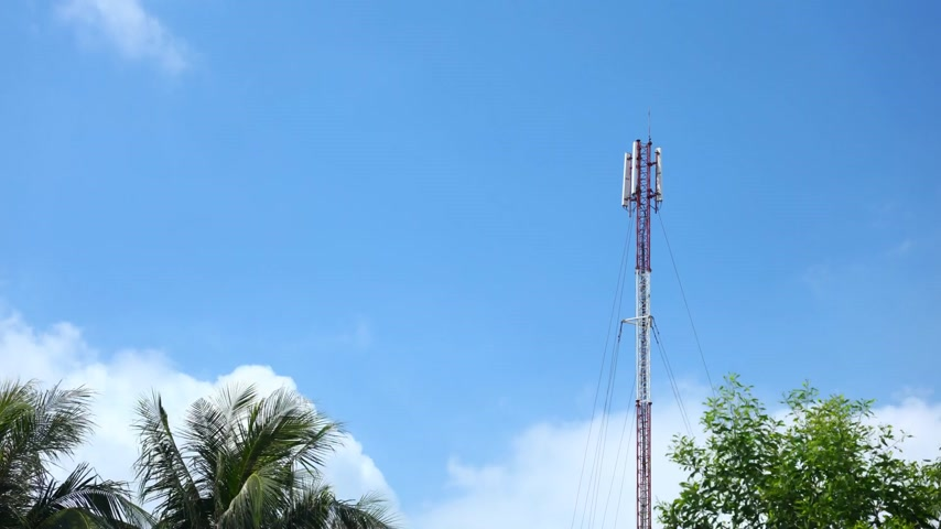 telecoms : Mobile communication mast in red and white time lapse with treetops and deep blue tropical cloudy skies.