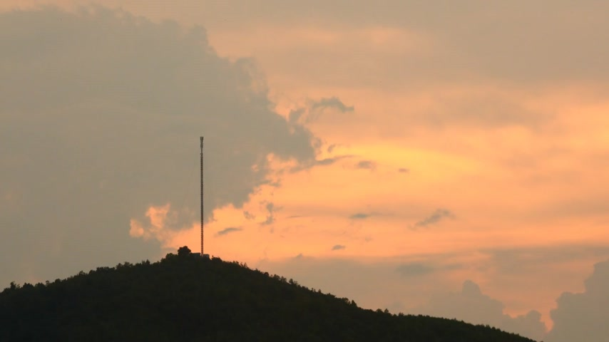 telecoms : Mobile data communication tower mast in silhouette on a mountain top with sunset orange red skies, treetops tropical cloudy skies time lapse. Stock Footage