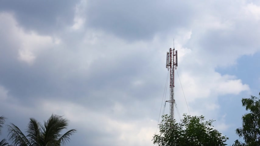 telecoms : Network communication mast tower time lapse red and white with treetops and deep blue tropical cloudy skies. Network broadcasting tower. Stock Footage