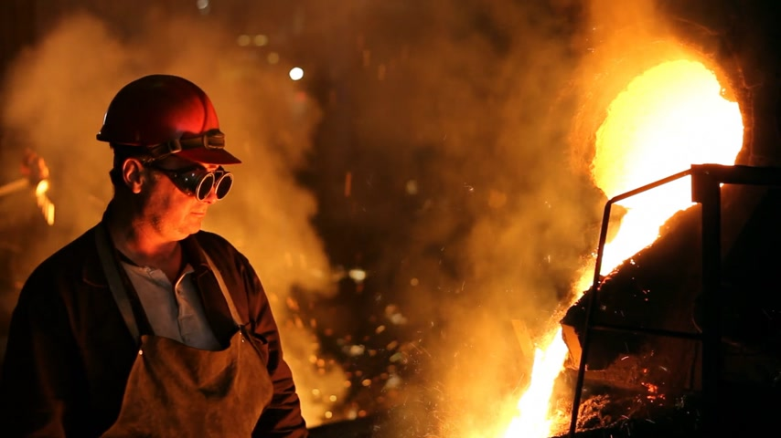 metal worker : Hard work in the foundry, worker watching and controlling iron smelting in furnaces, too hot and smoky workplace