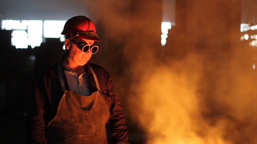 ferro : Hard work in the foundry, worker watching and controlling iron smelting in furnaces, too hot and smoky workplace. He takes off safety goggles