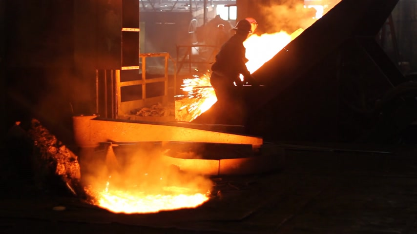 metal worker : Hard work in the foundry, worker controlling iron smelting in furnaces, too hot and smoky working environment