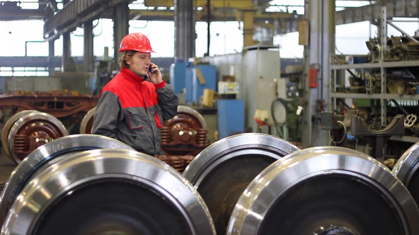 gyártó : Worker talking with a mobile phone about the quality of the wheels in factory overhaul of rail vehicles Stock mozgókép