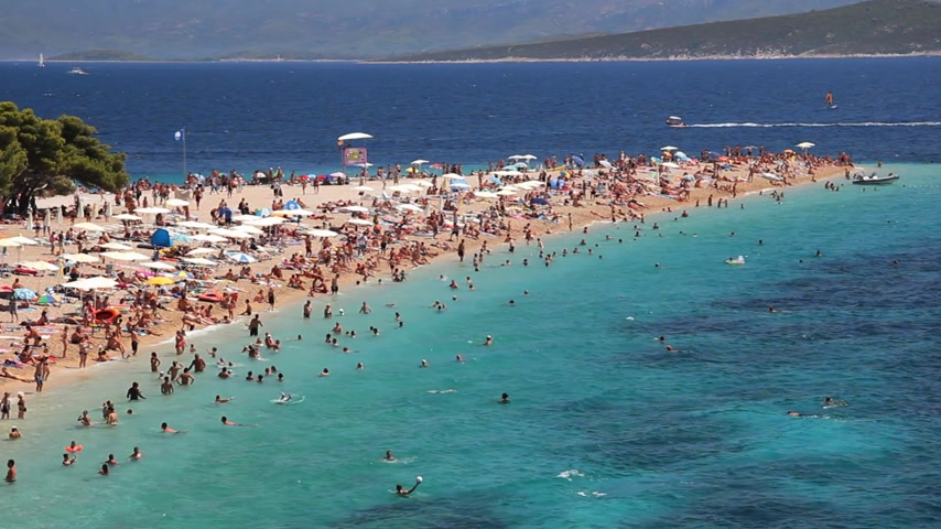 туристическим направлением : People on the beach, sunbathe and enjoy on vacation. Summertime at Adriatic Sea on the island Brac in Croatia