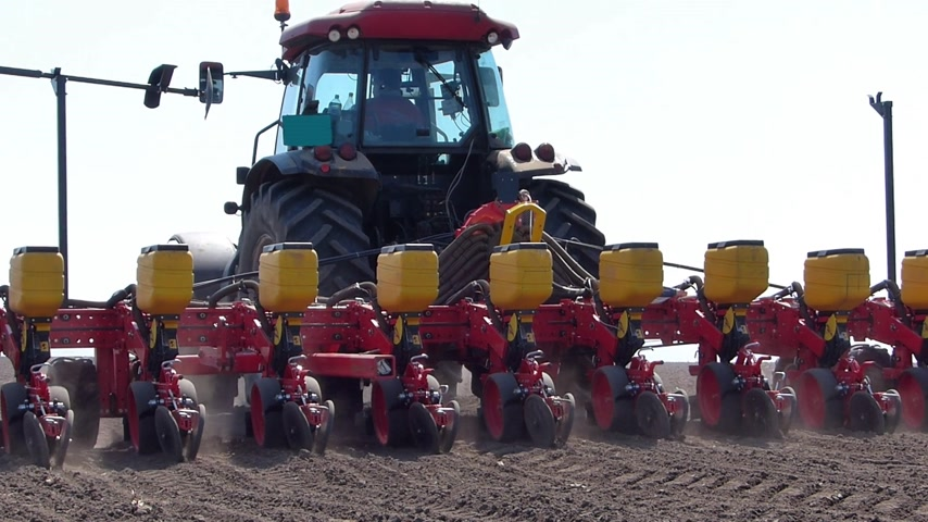 farm equipment : Agricultural tractor sowing and cultivating field Stock Footage