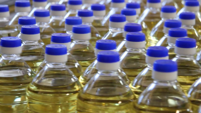 doldurmak : Sunflower oil in the bottle moving on production line in a factory Stok Video