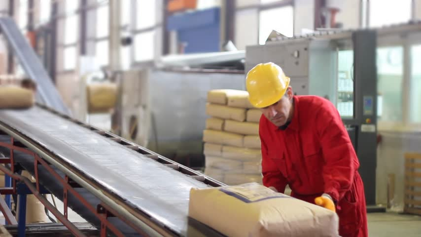 strojírenství : Worker controls sacks of sugar on the conveyor belt in a sugar factory