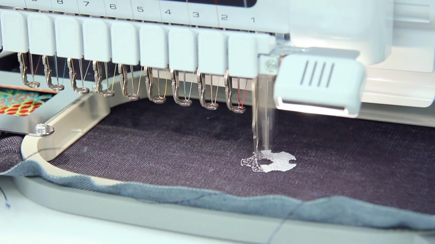máquina : Computerized machine embroidery working a soccer ball on jeans Stock Footage