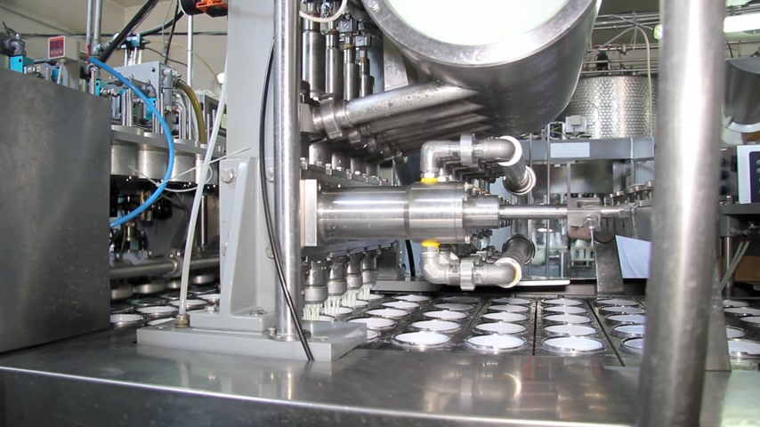йогурт : Production of yogurt in a dairy factory, industrial equipment for filling in plastic cups