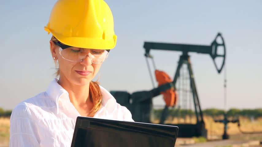 oil industry : Smiling female engineer in an oilfield working with notebook Stock Footage