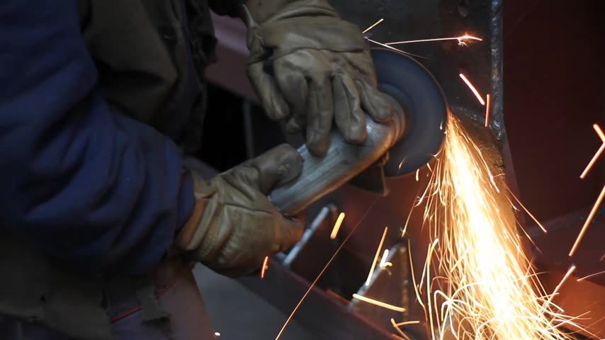 metal worker : Worker grinding a metal construction with grinding wheel in factory