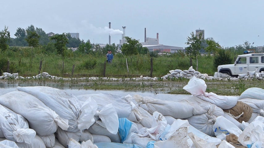 levee : Defense of the flooded river, in the foreground is a levee of sandbags, in the background is a police car and an industrial complex