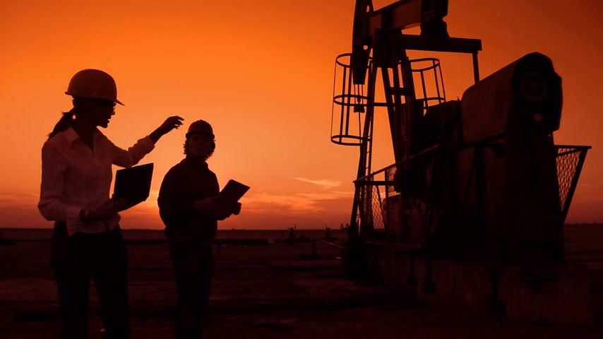 exploration : Oil pump jack and two oil workers at sunset, businesswoman with notebook and oil man