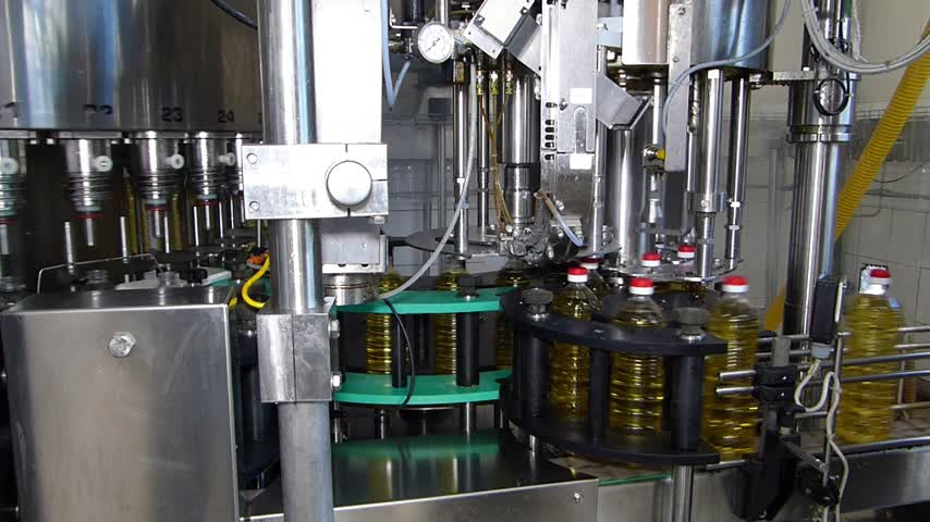 paketleme : Sunflower oil filling machine on automated production line. Machinery for bottling