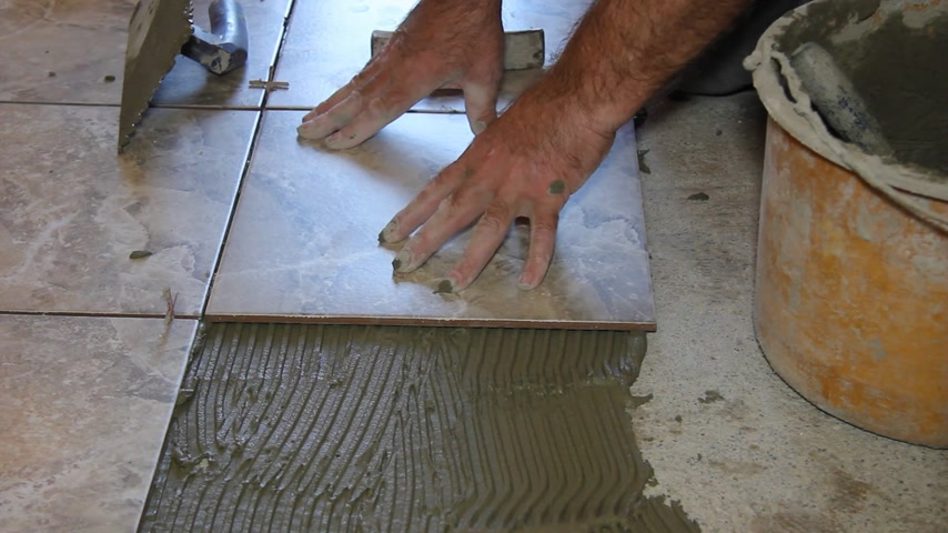 çini : Senior man putting tiles on the floor, interior decoration with ceramics