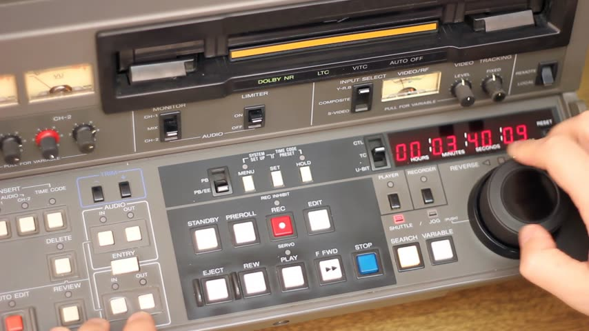 direto : Editor working on Betacam Sp recorder in Tv Studio, He turning and pushing shuttle and jog, and looking a footage on the tape Stock Footage