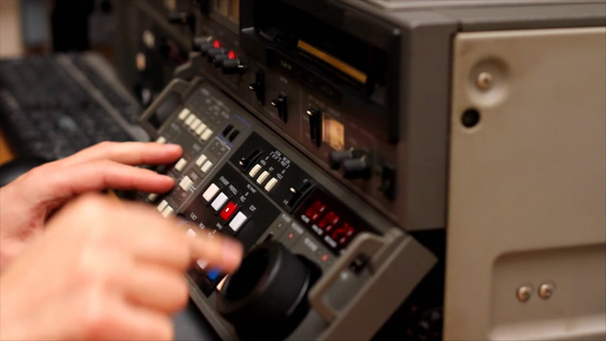 ntsc : Editor working on Betacam Sp recorder in Tv Studio, He turning and pushing shuttle and jog, and looking a footage on the tape Stock Footage