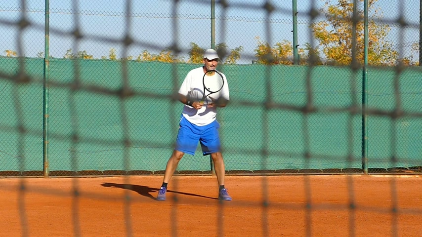 sztrájk : Man playing tennis on clay court, net in front