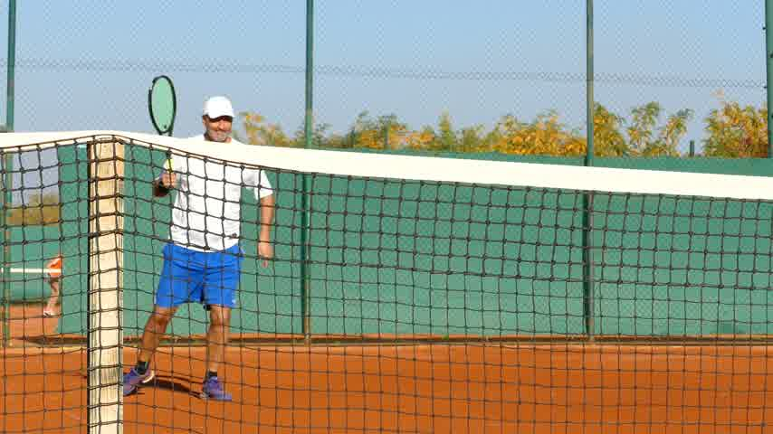teniszütő : Mature man playing tennis on clay court, warming up before the match, net in front Stock mozgókép