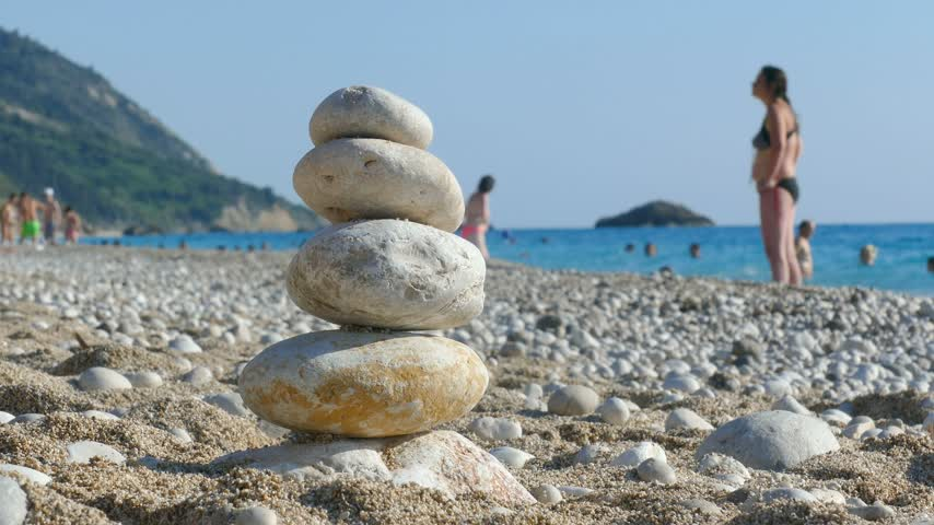 стабильность : The child plays with stones balance on beach, people sunbathe, swim and enjoy on sea vacation