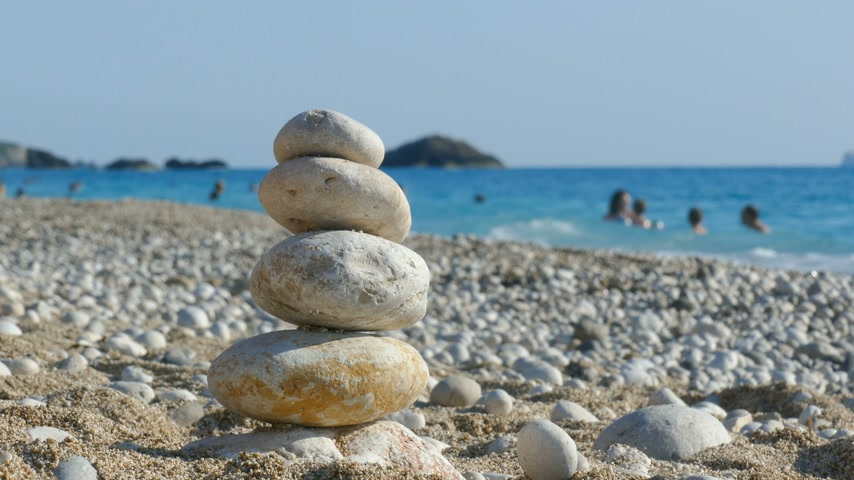stacked rock : The child plays with stones balance on beach, people sunbathe, swim and enjoy on sea vacation