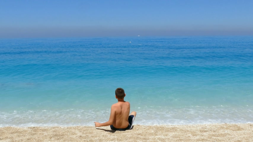 throws : The child throws pebbles into the sea and enjoy on sea vacation Stock Footage